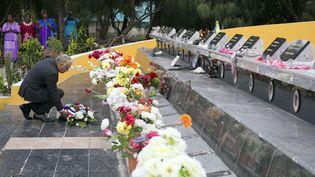 Le Premier ministre Jean-Marc Ayrault dépose une gerbe de fleurs, le 27 juilet 2013,sur lemonument à la mémoire des 19 militants kanaks tués lors de l'assaut de la grotte d'Ouvéa, 25 ans plus tôt en Nouvelle-Camédonie. (LIONEL BONAVENTURE / AFP)
