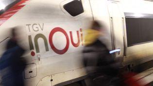 Des passagers marchent devant un TGV InOui de la SNCF en gare de Lille Flandres un soir de février 2020. (AURÉLIEN ACCART / RADIO FRANCE)