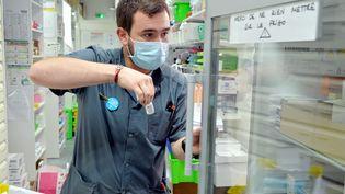 Un pharmacien tient un flacon de vaccin AstraZeneca dans son officine à Montpellier (Hérault), le 24 février 2021. (MAXPPP)