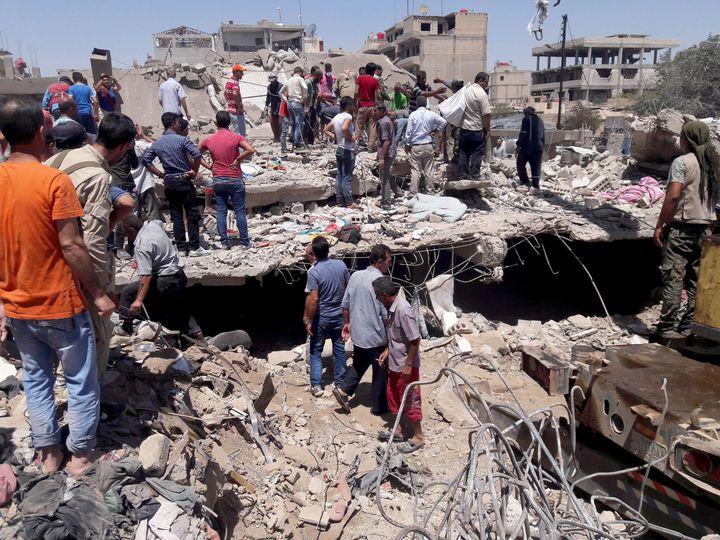 Des membres de la défense civile tentent, avec l'aide des habitants, de secourir les personnes piégées dans les décombres après l'attentat suicide, le 27 juillet 2016, dans la ville syrienne à majorité kurde de Qamichli. L'explosion qui a fait 44 morts et 140 blessés a été revendiquée par l'organisation de l'Etat islamique. (Habat Ahmed/ANADOLU AGENCY)