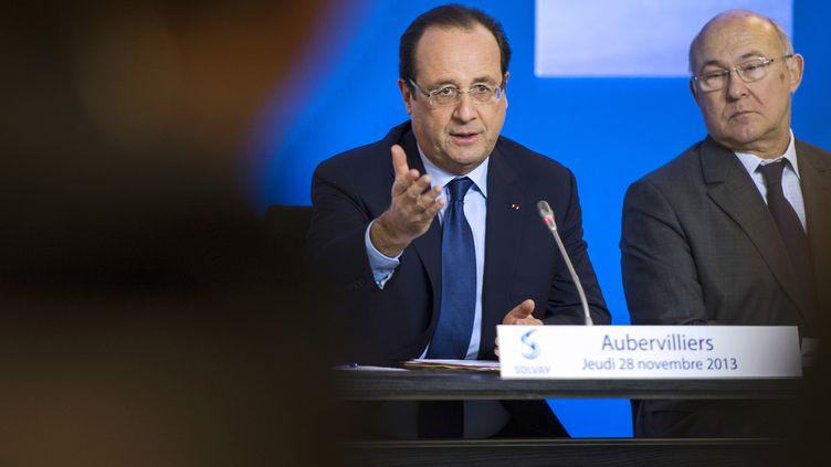 Le président de la République, François Hollande, et le ministre du Travail, Michel Sapin, lors d'une table ronde à Aubervilliers (Seine-Saint-Denis), le 28 novembre 2013. (ETIENNE LAURENT / AFP)