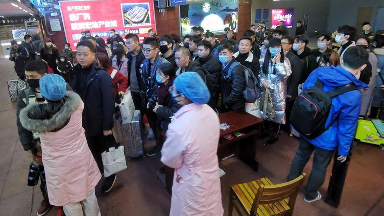 Le personnel médical vérifie la température corporelle des passagers arrivés dans une gare de la ville de Yingtan dans la province du Jiangxi (centre de la Chine) mercredi 22 janvier 2020. (HU GUOLIN / MAXPPP)