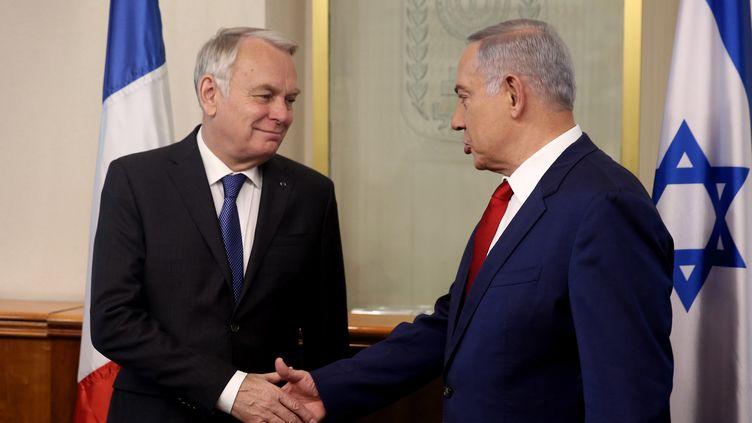 Le Premier ministre Benjamon Netanyahou serre la main du ministre des Affaores étrangères français Jean-Marc Ayrault, à Jérusalem, le 15 mai 2016. (MENAHEM KAHANA / AFP)