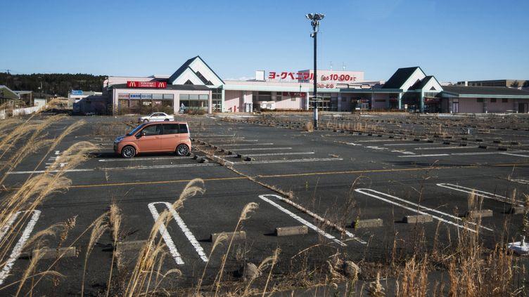 Personne sur le parking d'un supermarché, le 16 décembre 2013 à Tomioka. (GUILLAUME BRESSION / IRSN / AFP)