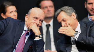 Alain Juppé et Nicolas Sarkozy lors d'un meeting du candidat des Républicains aux régionales enAquitaine-Limousin-Poitou-Charentes, à Limoges, le 14 octobre 2015. (NICOLAS TUCAT / AFP)