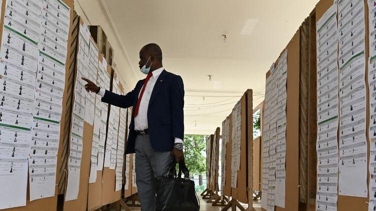 Un candidat vérifie son nom sur la liste des candidats aux élections législatives prévues le 6 mars, au siège de la Commission électorale à Abidjan, la capitale ivoirienne, le 1er février 2021. (ISSOUF SANOGO / AFP)