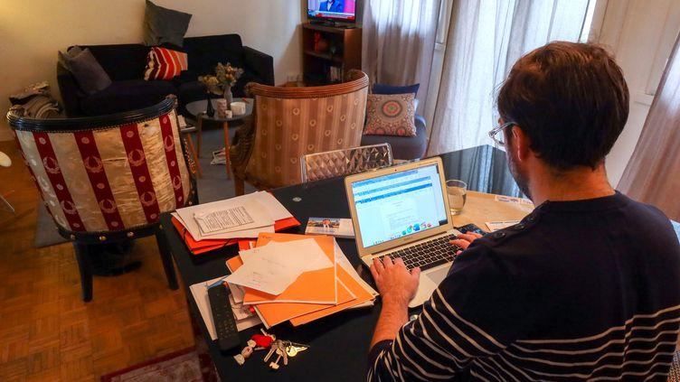 Un salarié travaille à domicile, le 13 mars 2020, alors que la France est confrontée à l'épidémie de coronavirus. (NICOLAS GUYONNET / AFP)
