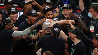 Les joueurs des Milwaukee Bucks célèbrent leur victoire face aux Atlanta Hawks autour du trophée de champion de laconférence Est, samedi 3 juillet 2021. (KEVIN C. COX / Getty Images via AFP)