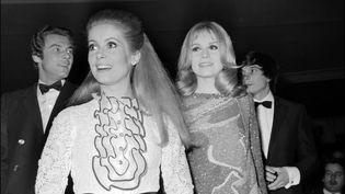 """Catherine Deneuve (à gauche) et sa sœur Françoise Dorléac (à droite) lors de la première des """"Demoiselles de Rochefort"""" le 8 mars 1967 à Paris (AFP)"""