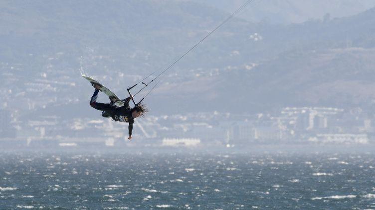 Un kitesurfeur au-dessus de l'océan le 6 février 2019 au Cap (Afrique du Sud). (RODGER BOSCH / AFP)