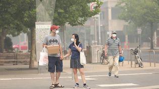 Des passants se protègent le visage avec des masques à Canberra. Dimanche 5 janvier, la capitale fédérale australienne est passée en tête des villes les plus polluées au monde,conséquencedes incendiesqui ravagent le sud du pays. (CHU CHEN / XINHUA)