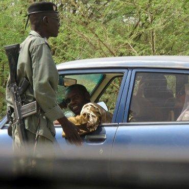 Un officier de la police camerounaise contrôle l'entrée de la petite ville de Fotokol, située à l'extrême nord du pays, afin de prévenir d'éventuelles attaques de la secte Boko Haram. (AFP PHOTO / REINNIER KAZE)