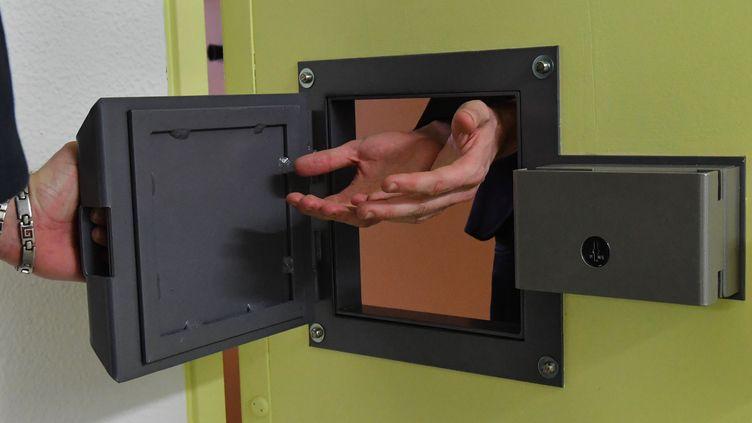 Un détenu présente ses mains pour être menotté dans l'unité pour détenus violents de la prison de Sequedin, près de Lille(Nord). (DENIS CHARLET / AFP)