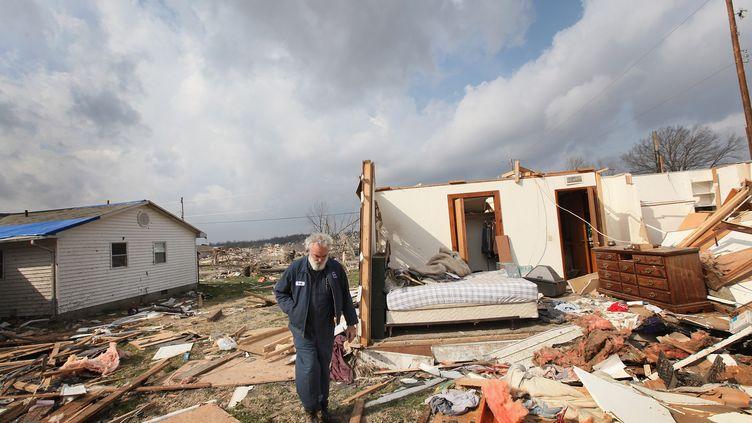 Un habitant de Harrisburg (Illinois) marche devant ce qu'il reste de sa maison, dévastée par le passage d'une tornade. (SCOTT OLSON / GETTY IMAGES / AFP PHOTO)