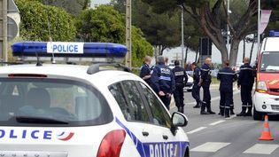 Des policiers et des pompiers se tiennent près du rond-point où le tireur présumé a été interpellé, à Istres (Bouches-du-Rhône), le 25 avril 2013. (GERARD JULIEN / AFP)