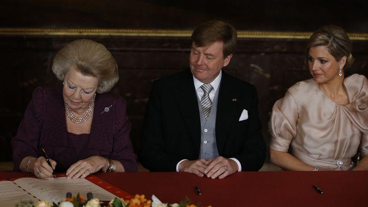 La reine Beatrix, aux côtés du prince Willem-Alexander et de son épouse Maxima,signe l'acte d'abdication, le 30 avril 2013, au palais royal d'Amsterdam (Pays-Bas). (BART MAAT / AFP)
