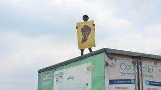 """Un manifestant, debout sur un camion, tient une pancarte où il est écrit : """"Ne jamais abandonner."""" Il participe à une manifestation pacifique contre les brutalités policières au Nigeria à Magboro, dans l'Etat d'Ogun, le 20 octobre 2020. (OLUKAYODE JAIYEOLA / NURPHOTO)"""