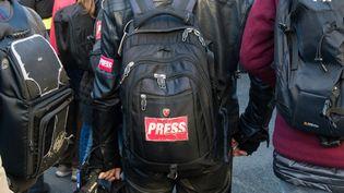 """Un homme avec un autocollant """"Press"""" sur son sac à dos lors d'une manifestatoin contre la réforme des retraites, à paris, le 16 janvier 2020. (RICCARDO MILANI / HANS LUCAS / AFP)"""