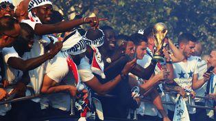 Les joueurs de l'équipe de France défilent sur les Champs-Elysées, lundi 16 juillet, et présentent le le trophée aux supporters. (ZAKARIA ABDELKAFI / AFP)
