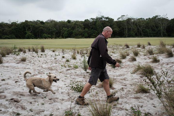 Neil Cleverly, le gérant du parcours, enlève les mauvaises herbes pour éviter leur prolifération, le 23 novembre 2016. (YASUYOSHI CHIBA / AFP)