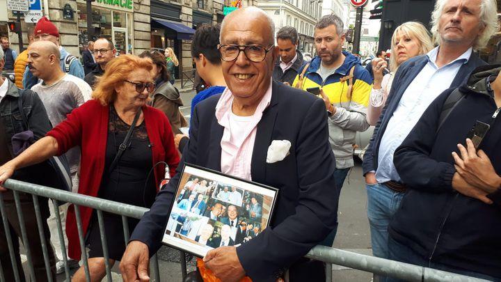 Omar Kerkoudi, un fan de Jacques Chirac venu rue de Tournon avec des photos de l'ancien président et lui. (RADIO FRANCE / SANDRINE ETOA ANDEGUE)