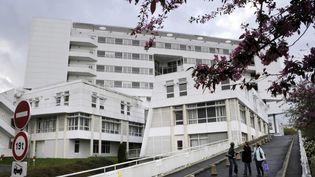 Des personnes passent devant l'hôpital de Pontchaillou à Rennes (Ille-et-Vilaine), où six patients sont hospitalisés après un essai thérapeutique qui a mal tourné, le 15 janvier 2016. (DAMIEN MEYER / AFP)