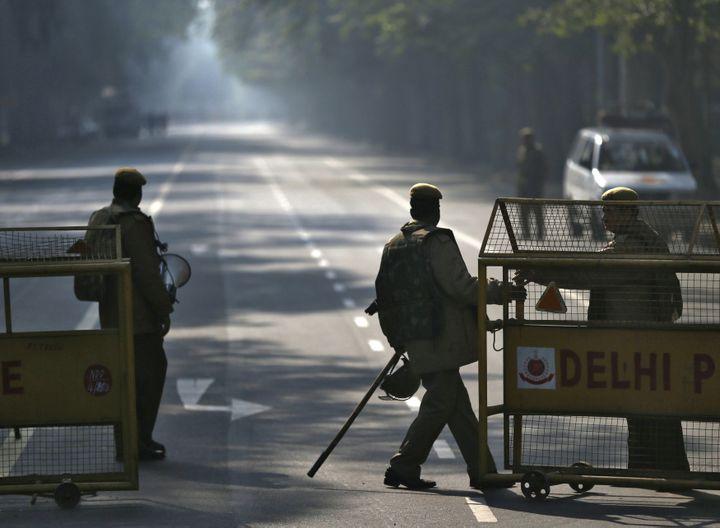 Des policiers indiens déployant des barrières pour prévenir toute manifestation, le 29 décembre à Delhi (Inde), au lendemain de la mort de l'étudiante de 23 ans violée par six hommes. (AHMAD MASOOD / REUTERS)