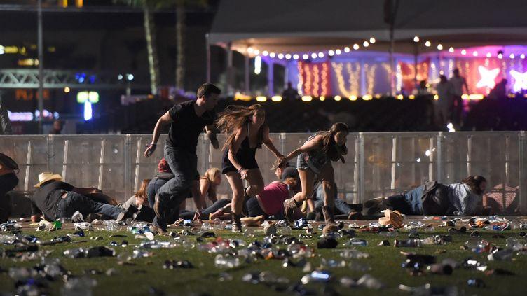 Des gens s'enfuient et tentent de se protéger, lors de la fusillade survenue à Las Vegas, le 1er octobre 2017. (DAVID BECKER / GETTY IMAGES NORTH AMERICA / AFP)