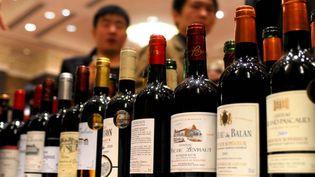 Des bouteilles de vins exposées et dégustées pendant la fête du vin, à Bordeaux (Gironde), le 12 novembre 2011, attirent l'attention d'experts chinois. (XIAO YIJIU / XINHUA / AFP)