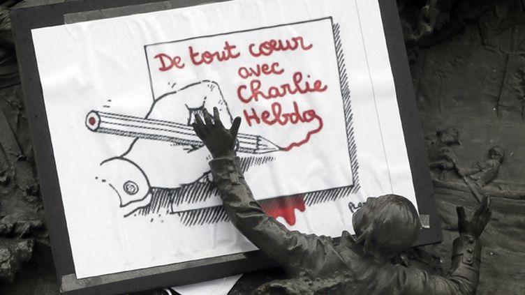 (Un dessin de Plantu est déposé au pied de la statut de la République à Paris au lendemain de l'attaque terroriste contre Charlie Hebdo © Maxppp)