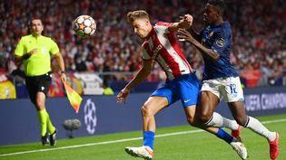 Marcos Llorente (Atlético Madrid, à gauche) face au défenseur de Porto Zaidu Sanusi au Wanda Metropolitano, le 15 septembre 2021. (GABRIEL BOUYS / AFP)