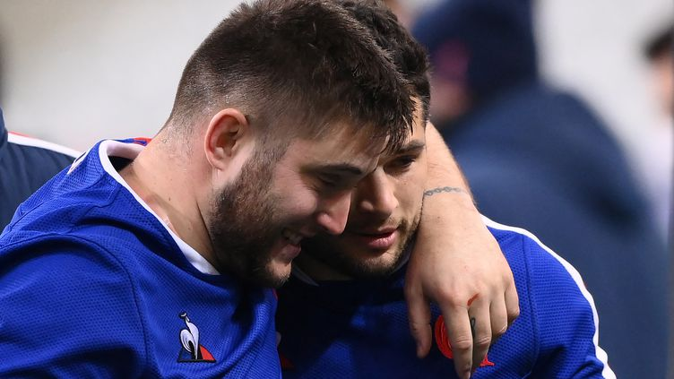 Le pilier gauche du XV de France Cyril Baille célèbre la victoire française contre le Pays de Galles avec l'arrière Brice Dulin, le 20 mars 2021 au Stade de France. (FRANCK FIFE / AFP)