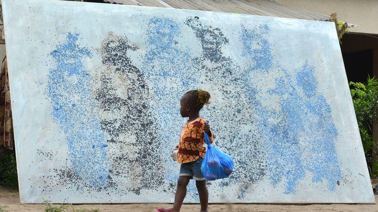L'artiste ivoirien Lanin Saint-Etienne Yeanzi réalise des œuvres avec des sacs en plastique fondus. L'un de ses tableauxétait exposé à Bingerville, près d'Abidjan, en septembre 2015. (ISSOUF SANOGO / AFP)