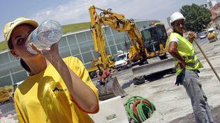 Des ouvriers sur le chantier du Palais des sports de Toulouse (Haute-Garonne), le 19 juillet 2006. (LIONEL BONAVENTURE / AFP)
