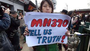 """Une proche d'une victimes chinoise demande """"la vérité"""" sur la disparition du vol MH370, lors d'une manifestation à Pékin (Chine), dimanche 8 mars 2015. (GOH CHAI HIN / AFP)"""