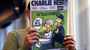 """Un homme lit l'hebdomadaire """"CharlieHebdo"""" du 19 septembre 2012, à Paris. (THOMAS COEX / AFP)"""