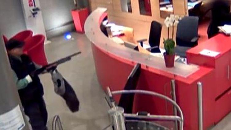 Capture d'écran des images de vidéosurveillance de BFMTV, où l'on voitun homme armé dans le hall de la chaîne, vendredi 15 novembre. (BFMTV / FRANCETV INFO)