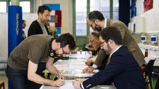 Un électeur émarge sur les listes électorales dans un bureau de vote du 11e arrondissement de Paris, le 26 mai 2019,après avoir voté aux élections européennes. (DENIS MEYER / AFP)
