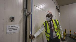 Peter Musola, responsable du fret à l'aéroport international de Nairobi (Kenya), le 11 février 2021 devant la chambre froide où les doses de vaccins pourraient être stockées. (TONY KARUMBA / AFP)
