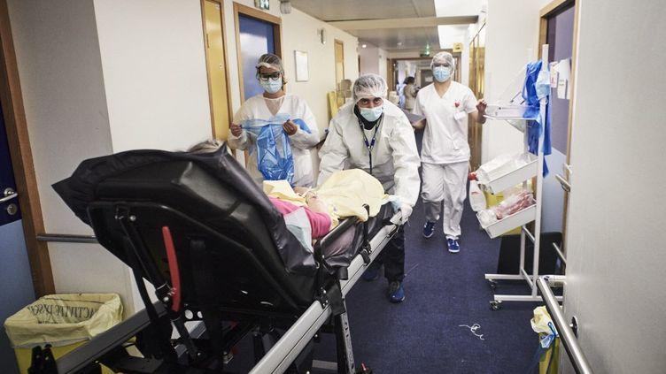 Des ambulanciers transportent un patient atteint par le Covid-19, le 6 mai 2021 àl'Institut Mutualiste Montsouris à Paris. (ANTONIN BURAT / HANS LUCAS / AFP)
