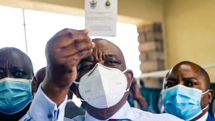 Le vice-président et ministre de la Santé du Zimbabwe, Constantino Chiwenga, brandit son certificat de vaccination après avoir reçu la première injection deSinopharm, le vaccin chinois contre le Covid-19, le 18 février 2021. (JEKESAI NJIKIZANA / AFP)