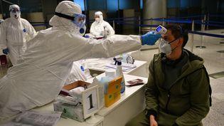 Un médecin contrôle un passager, le 19 mars 2020 à l'aéroport Sheremetyevo de Moscou (Russie). (RAMIL SITDIKOV / SPUTNIK / AFP)