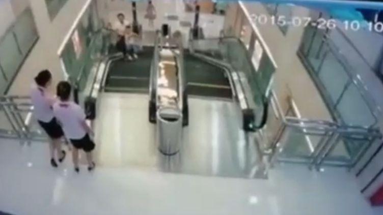 Capture d'écran de la vidéo montrant une femme happée par un mécanisme d'escalator après avoir sauvé son fils, àJingzhou (Chine), le 25 juillet 2015. (IMAGINECHINA / AFP)