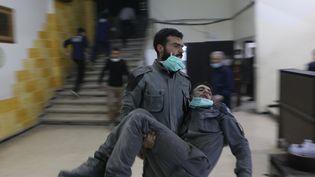 Un homme portant secours à un blessé, touché par une attaque au gaz chimique dansun hôpital de la Ghouta orientale, le 8 mars 2018. (MOHAMMAD AL SHAMI / ANADOLU AGENCY)