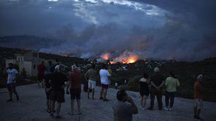 Des personnes regardent le feu à Rafina (Grèce) le 23 juillet 2018. (ANGELOS TZORTZINIS / AFP)