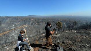 Des volontaires aident les pompiers à déblayer des terrains ravagés par l'incendie, le 14 avril 2014, à Valparaiso (Chili). (MARTIN BERNETTI / AFP)