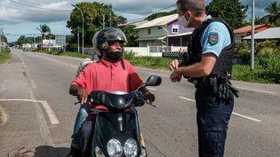 Un gendarme contrôle un motard, le 20 juin 2020 à Cayenne, en Guyane. (JODY AMIET / AFP)