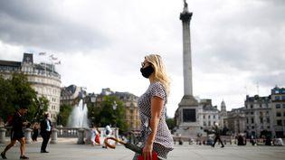 Une femme masquée dans les rues de Londres, à Trafalgar Square, le 21 août 2020. (HENRY NICHOLLS / REUTERS)