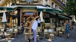Les employés de la brasserie LesDeux Magots préparent la terrasse pour la réouverture, le 1er juin 2020 à Paris. (BERTRAND GUAY / AFP)