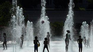 Des enfants se rafraîchissent durant un épisode de canicule dans une fontaine du parc André Citroën, à Paris, le 26 juillet 2018. (ALAIN JOCARD / AFP)